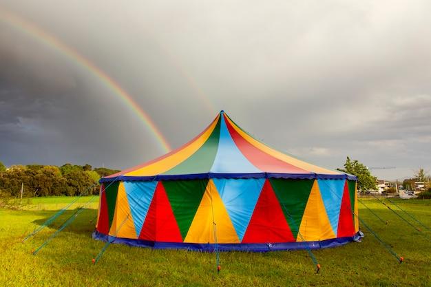 Gekleurde circustent op een regenachtige dag met een regenboog aan de hemel