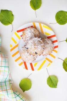 Gekleurde cupcakes op een plaat met groene bladeren en handdoek