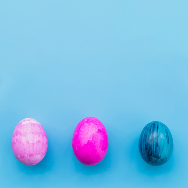 Gekleurde drie eieren op blauwe achtergrond