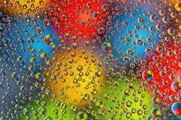 Gekleurde druppels water op glas. abstracte textuur als achtergrond