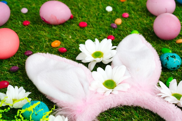 Gekleurde eieren en levendige snoepjes op gras. pasen samenstelling