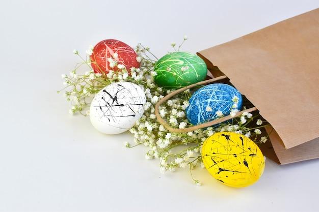 Gekleurde eieren in een papieren zak. levering met pasen.