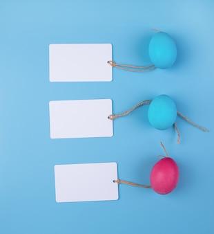 Gekleurde eieren met lege markeringen die op blauwe hoogste mening worden geïsoleerd als achtergrond