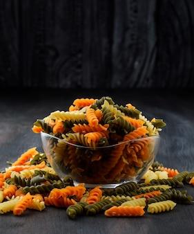 Gekleurde fusilli pasta in een glazen kom