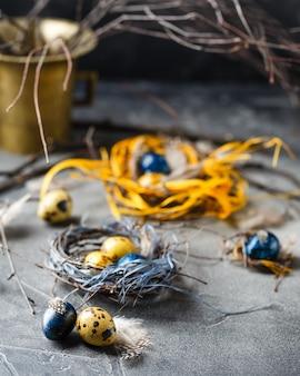 Gekleurde gele en blauwe paaseieren in kleine nesten. kwarteleitjes voor katholieke en orthodoxe paasvakantie.