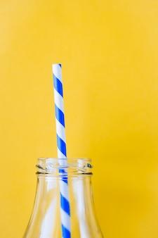 Gekleurde, gestreepte rietjes om sap of cocktail te drinken, in een glazen fles