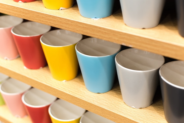 Gekleurde glazen op planken in winkel. ups van alle kleuren van de regenboog op de toonbank van de winkel