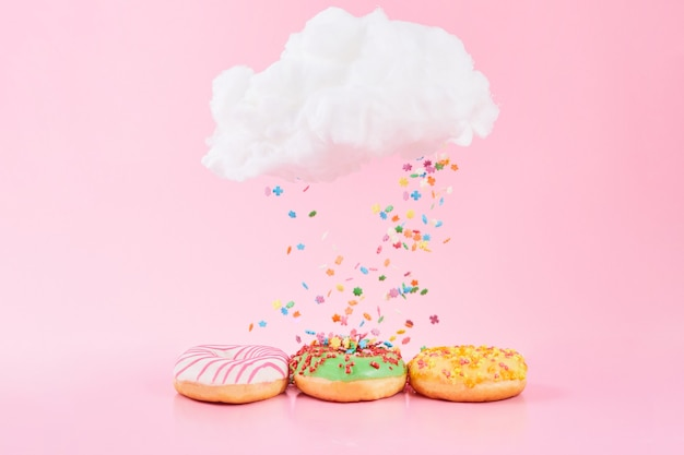 Gekleurde hagelslag valt uit de wolk. geassorteerde donuts frosted, roze geglazuurd en hagelslag op roze achtergrond.