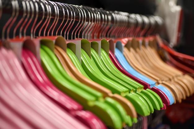 Gekleurde hangers hangen in de kledingkast van de winkel