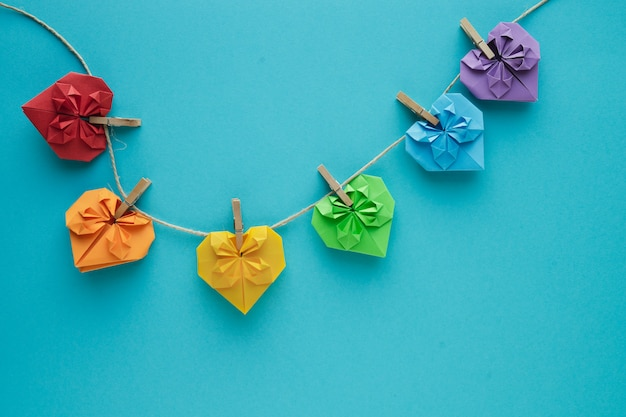 Gekleurde harten opgehangen aan touw met houten clips op een blauwe achtergrond. kopieer ruimte. valentijnsdag concept. lgtb gay concept.