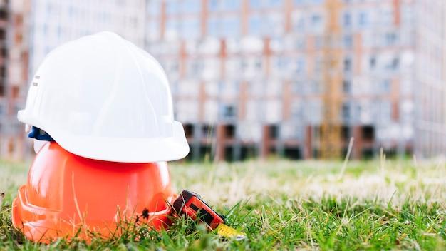 Gekleurde helmen met meetlint op het gras