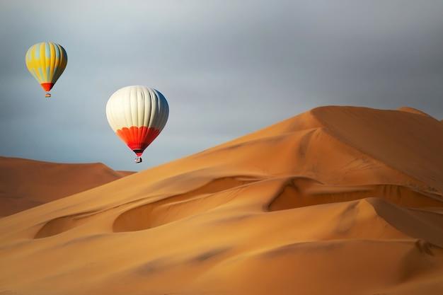 Gekleurde heteluchtballonnen die bij zonsondergang over de zandduinen vliegen