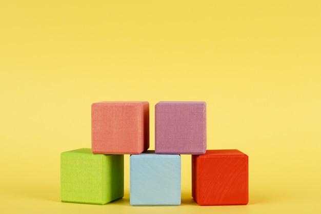 Gekleurde houten kubussen op gele achtergrond