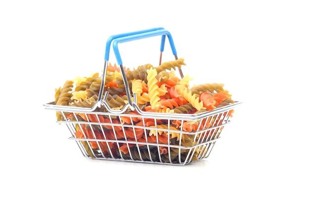 Gekleurde italiaanse pasta in een mandje van de markt op een witte achtergrond. meelproducten en voedsel bij het koken