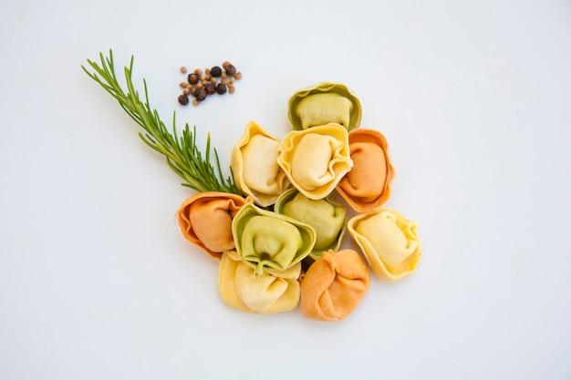 Gekleurde knoedels en kruiden op een lichte ondergrond. italiaans eten, ongekookte ravioli met kruiden, geïsoleerd