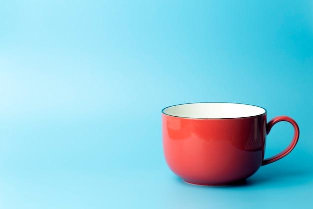 Gekleurde kop op een lege gekleurde achtergrond, minimale conceptenachtergrond. thuis kookgerei en ochtendidee.