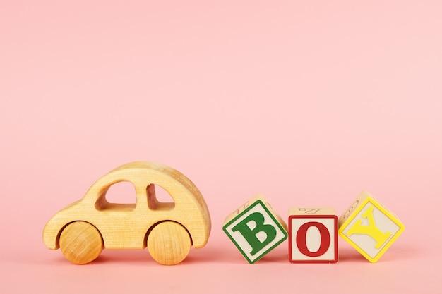 Gekleurde kubussen met letters jongen en auto speelgoed op een roze