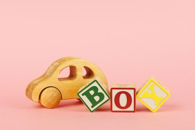 Gekleurde kubussen met letters jongen en speelgoed op een roze