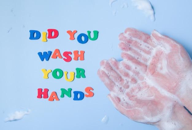 Gekleurde letters: heb je je handen naast je handen gewassen in foam op een gekleurde achtergrond