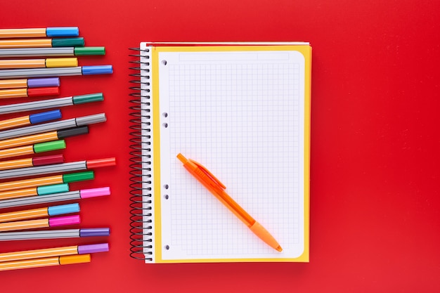 Gekleurde markeringen en een notebook op een rode achtergrond. terug naar schoolconcept en ambachten.