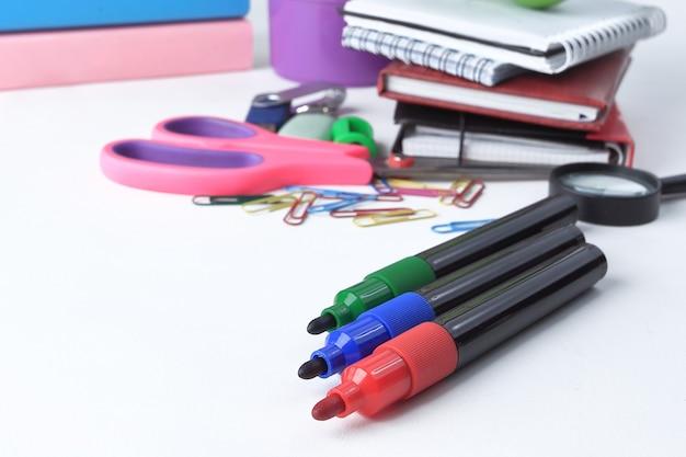 Gekleurde markeringen en schoolbenodigdheden op een witte achtergrond .concept van onderwijs