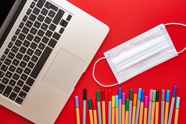 Gekleurde markeringen, masker en laptop op een rode tafel. terug naar schoolconcept en bescherming tegen het covid-virus.