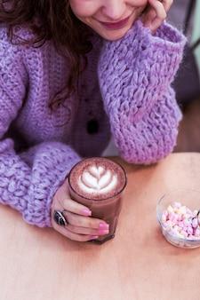Gekleurde marshmallow. mooie glimlachende dame in oversized paarse trui en met donkere omvangrijke accessoires