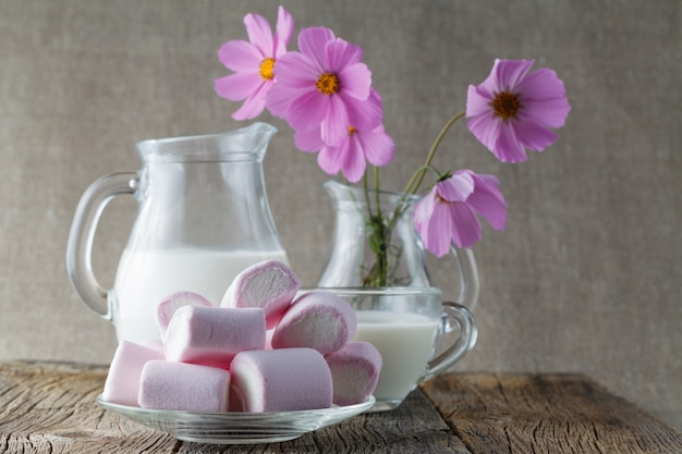 Gekleurde mashmallow met melk op houten tafel