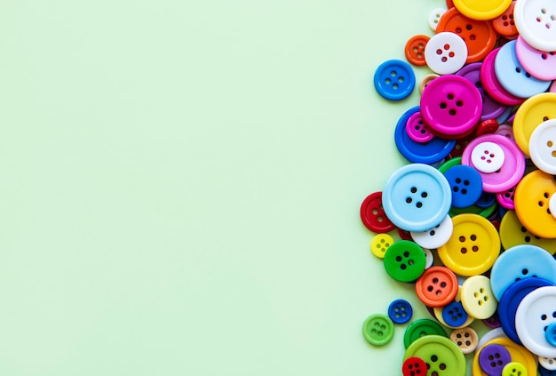 Gekleurde naaien knoppen samenstelling op groene pastel achtergrond