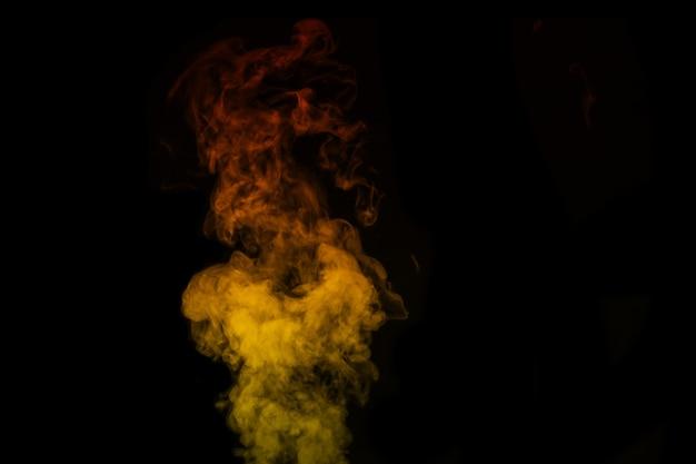 Gekleurde oranjegele stoom, rook op een zwarte achtergrond om op uw foto's te leggen. geeloranje rook, stoom, aroma. maak mystieke halloween-foto's. abstracte achtergrond, ontwerpelement