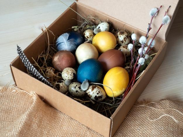 Gekleurde paaseieren, kwarteleitjes in een doos met stro op een ruwe doek en houten achtergrond