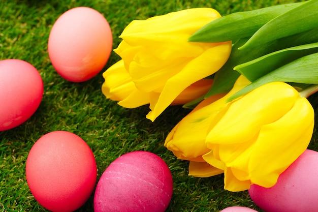 Gekleurde paaseieren op gras versierd met bloemen
