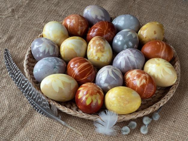 Gekleurde paaseieren worden in rieten bakjes op een ruwe doek gelegd