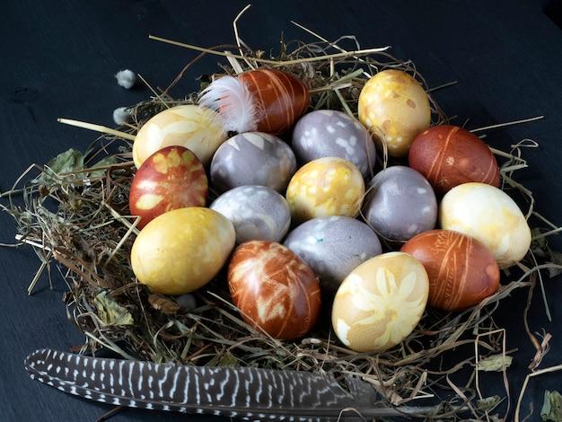Gekleurde paaseieren worden op een stro-nest en een zwarte houten tafel gelegd