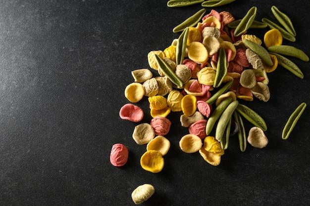 Gekleurde pasta verspreid over de tafel