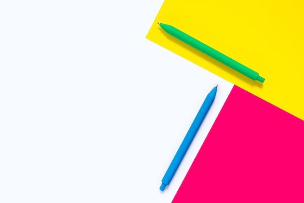 Gekleurde pennen op witte achtergrond met roze en gele elementen.