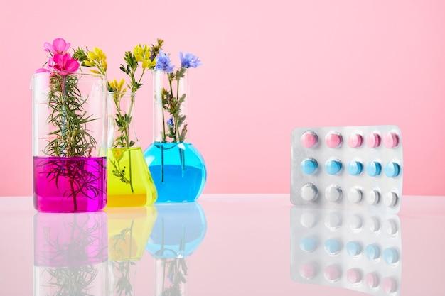 Gekleurde pillen en reageerbuizen met planten op een roze achtergrond. concept van natuurlijke drug.