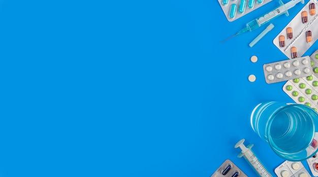 Gekleurde pillen en tabletten op een blauwe achtergrond met kopie ruimte