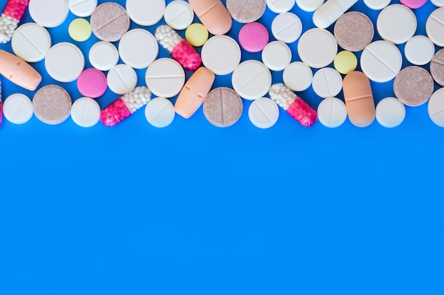 Gekleurde pillen op een blauwe achtergrond.