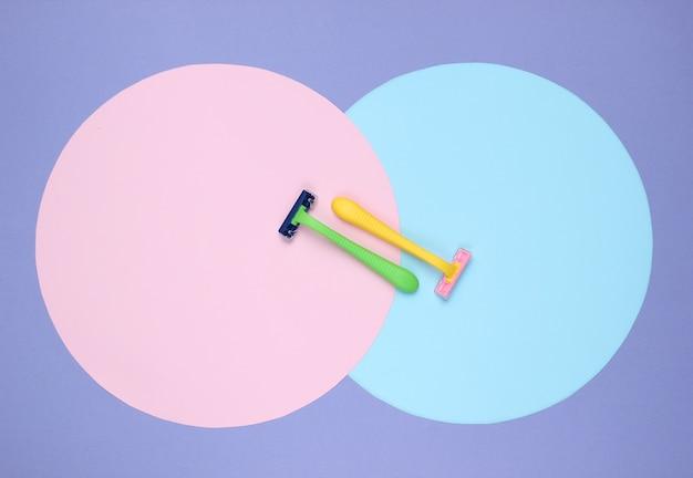 Gekleurde plastic scheermessen op paarse achtergrond met roze blauwe pastelkleurcirkels. minimalistisch schoonheidstilleven