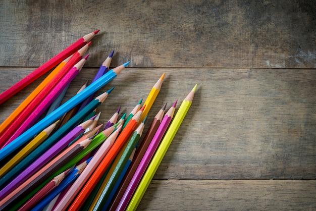 Gekleurde potloden en notitieboekje op een houten