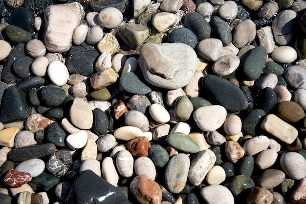 Gekleurde ronde kleine steentjes aan de kust