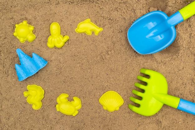 Gekleurde schop en hark en mallen in zandbak. zandspeelgoed voor buiten voor kinderen. zomer concept. met plaats voor tekst.