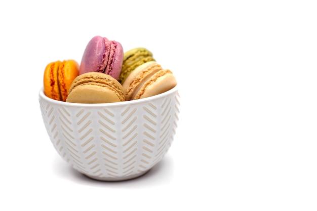 Gekleurde smakelijke zelfgemaakte organische bitterkoekjes die in ceramische plaat op wit geïsoleerde achtergrond liggen