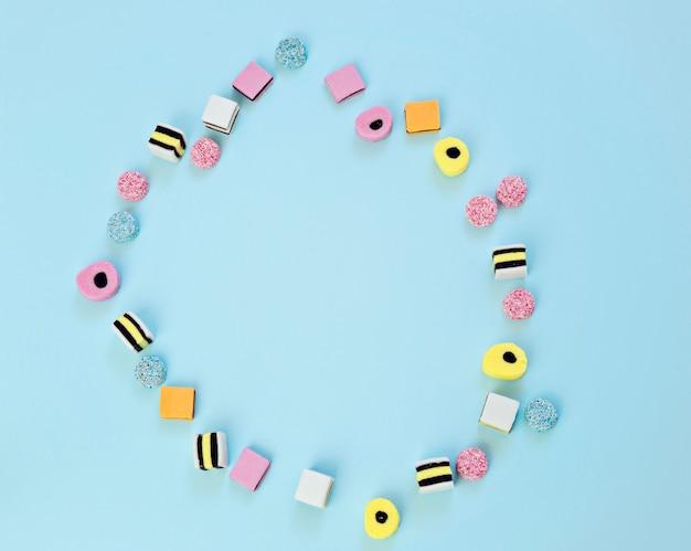 Gekleurde snoepjes zijn verspreid over een blauwe achtergrond