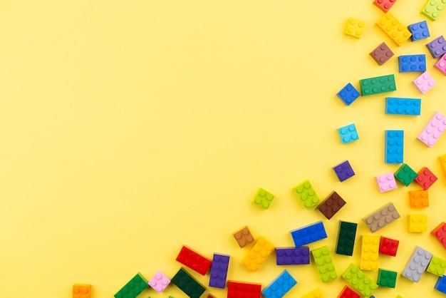 Gekleurde speelgoedbakstenen met ruimte voor tekst. stuk speelgoed gele achtergrond.