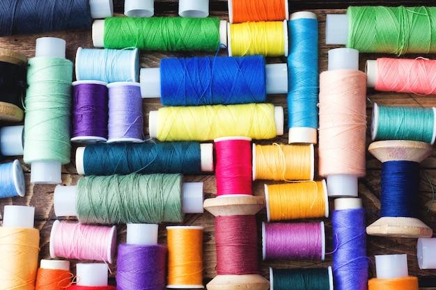 Gekleurde spoelen van draad die in rijen op houten oppervlakte worden opgemaakt