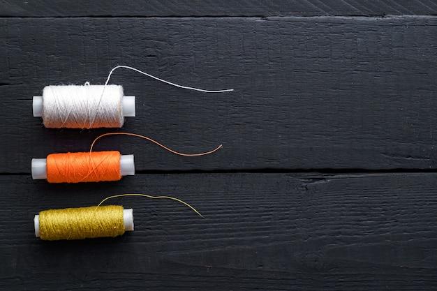 Gekleurde spoelen van draad voor het naaien op een houten zwarte achtergrond. kopieer ruimte