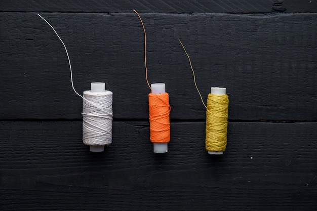 Gekleurde spoelen van draad voor het naaien op een houten zwarte ondergrond