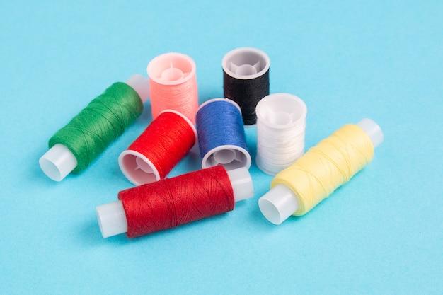 Gekleurde spoelen van naaigaren op een blauw